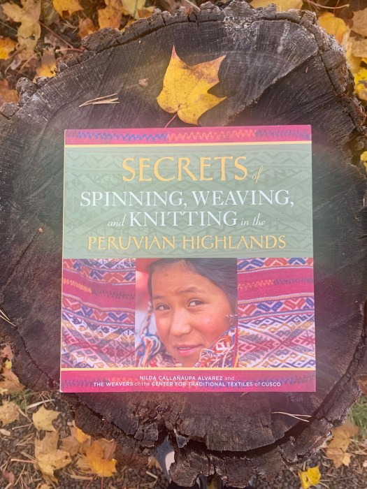 A book on a tree trunk. Secrets of Spinning, Weaving, and Knitting in the Peruvian Highlands by Nilda Callañaupa Alvare