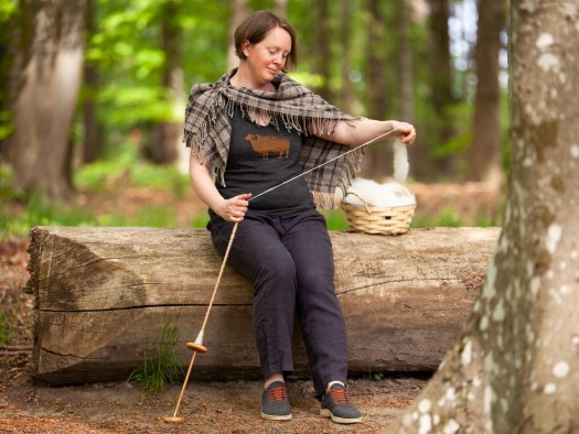 A woman spinning on a ground-resting spindle. She is sitting on a tree trunk in a spring forest.