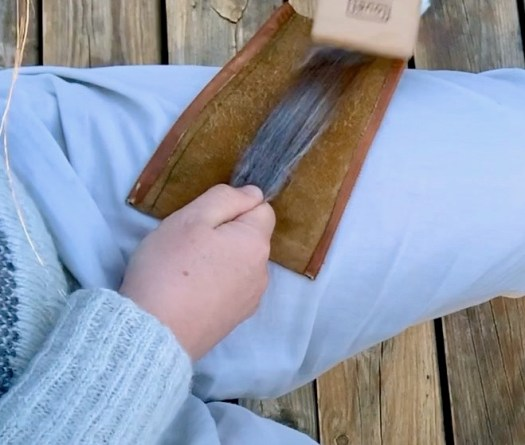 Close-up of a person carding a wool staple. A leather patch is underneath the wool. One hand is holding the staple at the far cut end while the other hand is holding the card that is carding the tip end.
