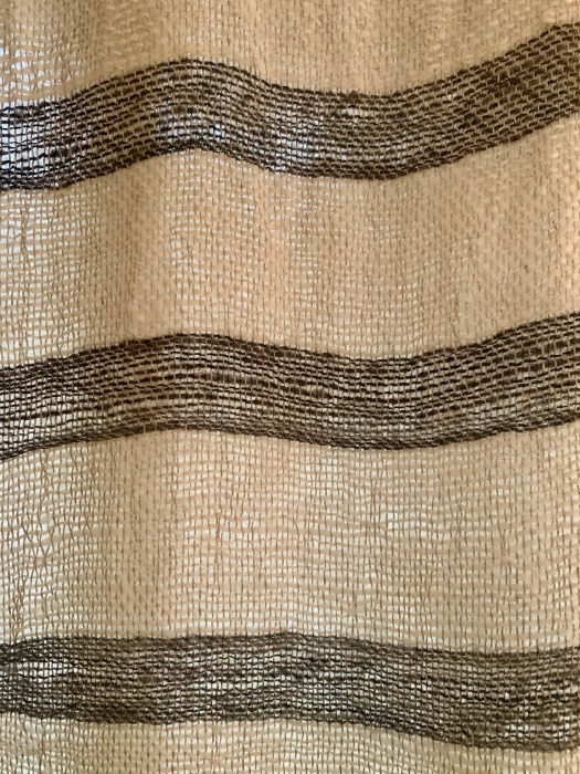 A loosely woven fabric in natural white with dark grey stripes.