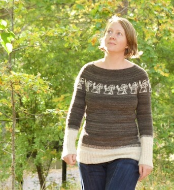 A woman walking outdoors. She is wearing a grey sweater with white spinning wheels in a stranded knitted yoke.
