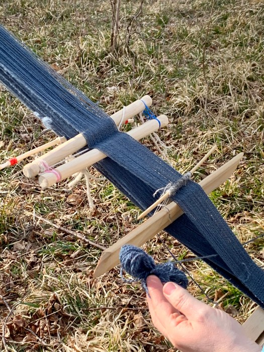 Close-up of a backstrap loom. Wooden sticks and rods attached between blue warp threads. A hand is pulling a piece of yarn through the shed.
