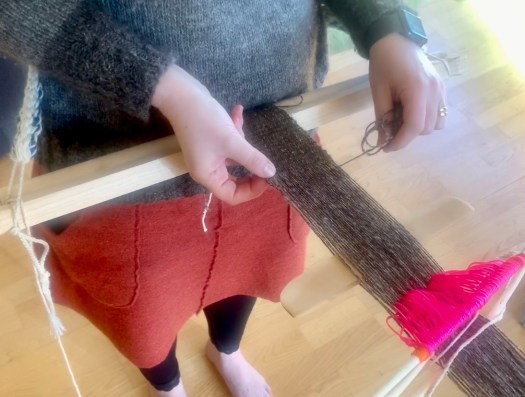 A person weaving on a Backstrap Loom. The warp yarn is natural brown. The heddle yarn is bright pink.