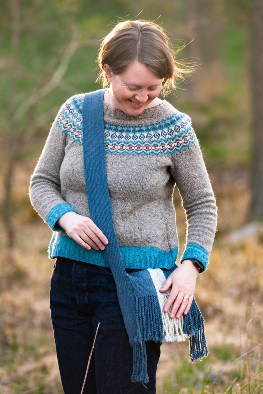 A smiling woman wearing a shoulder bag across her torso. The bag is blue and has fringes.