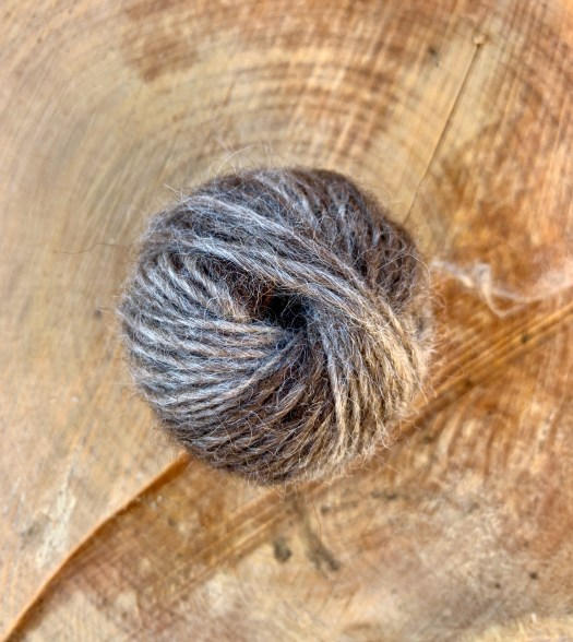 A finished little ball of yarn. Värmland wool hand carded into rolags and spun with long draw on a floor supported Navajo style spindle. 12-ish wpi. 11 grams, 36 meters, 3234 m/kg before fulling.