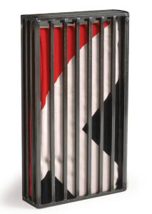 A concrete book resembles a cage. Inside of that cage is a red, white, and black pattern, resembling the Nazi flag.