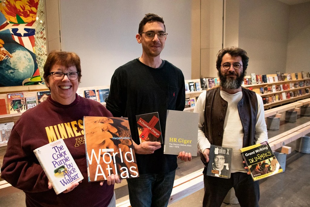 Librarian Betsy Friesen, artist Daniel McCarthy Clifford, and curator Boris Oicherman standing together in the Target Studio, holding books banned in U.S. prisons.