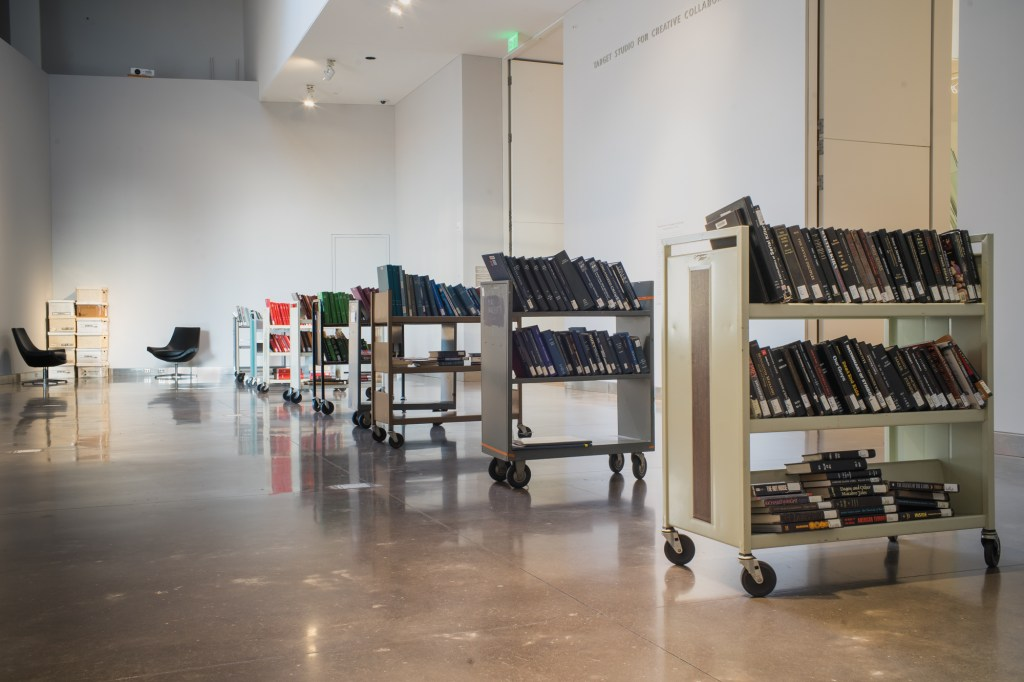 A view of Daniel's installation in the Target Studio, with a number of small shelves on wheels containing color-coordinated disapproved books.