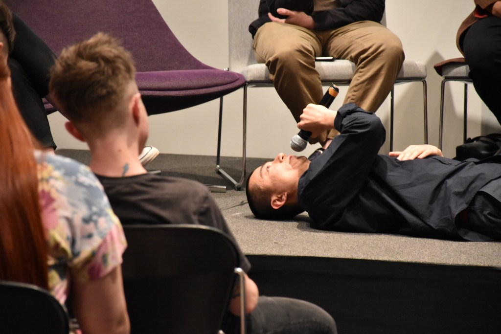 Peng Wu lies on his back on stage, looking up to the ceiling; the frame includes two audience members watching him.