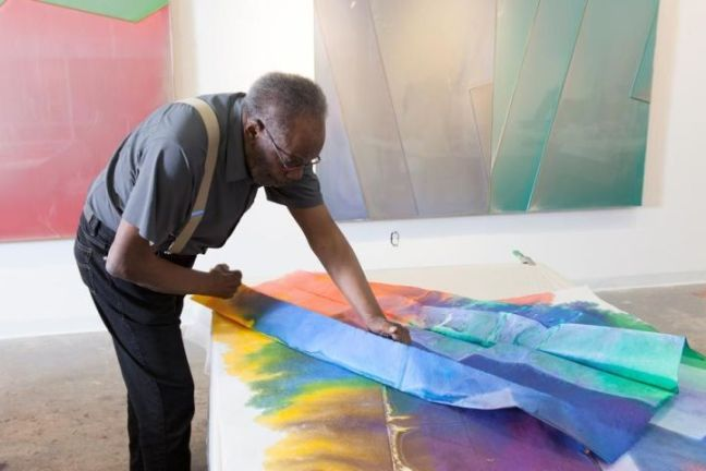 The artist is in a gallery, working over a colorful canvas.