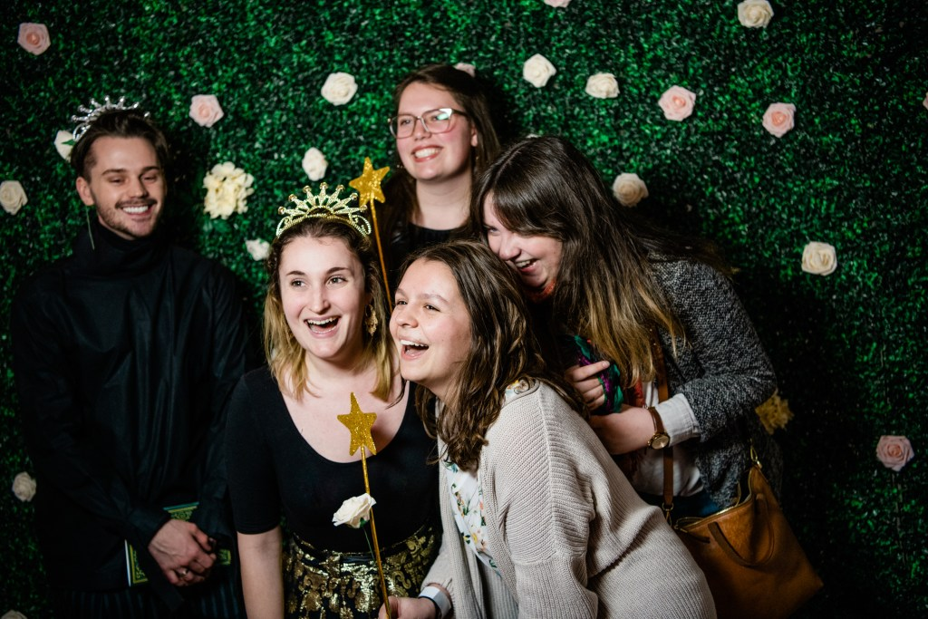 Five students pose, laughing with props, at a photobooth in front of a floral background.