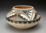 Cream colored pot with geometric black and red design covering the upper two-thirds of the pot.