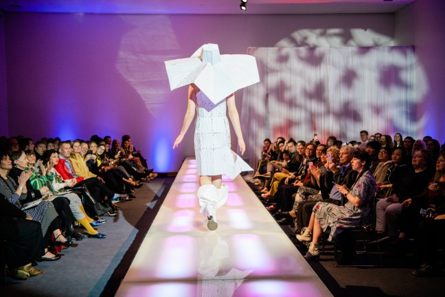 An image from the 2019 Student Design Showcase where somebody wearing a white garment with a massive white hat has their back turned to the camera and is walking down the runway. On both side of the walk, audience members are seated and cheering.