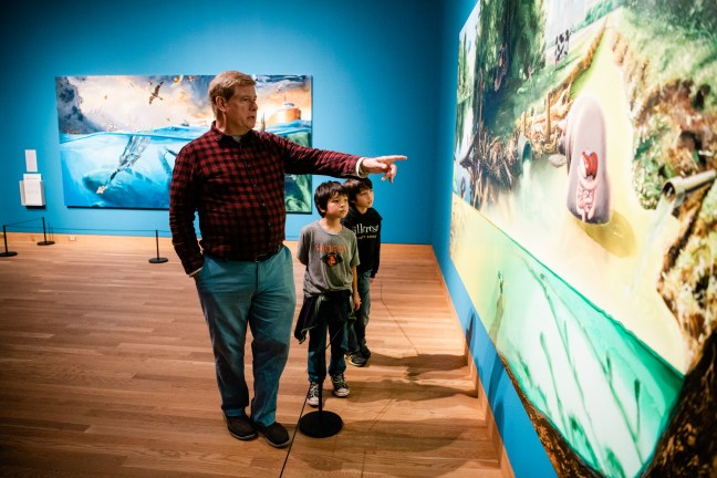 An older white man points out an image to two younger children, who look at the painting with interest.