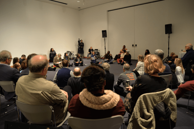 About four dozen people sit in a circle—some in chairs, some on the floor—in a large, otherwise empty white-walled room. Most have their attention fixed to a speaker who is sitting on the floor at the far end of the image. The image is from the November roundtable.