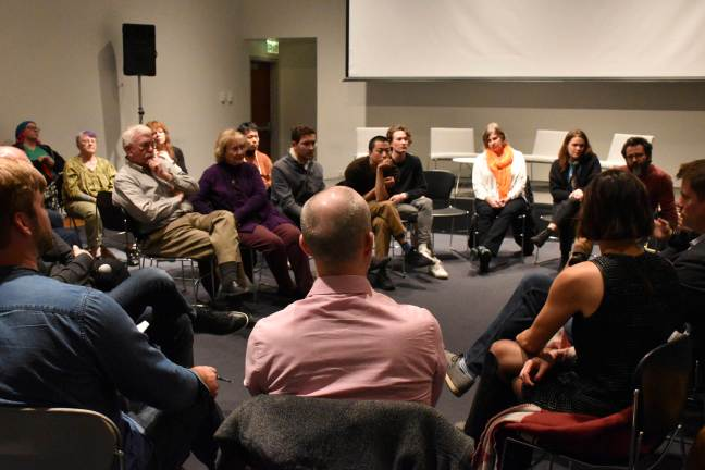 A group of about two dozen people sit in chairs positioned in a circle, all looking at a single speaker who is holding a microphone. The conversation is taking place in an empty-walled gallery space.