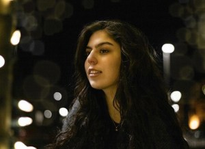 A photo of Ozge at night, looking away from the camera. Behind her are streetlights and a dark sky.