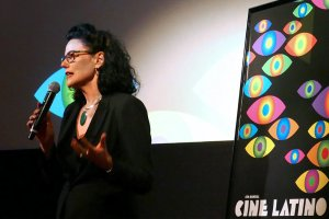 Hebe Tabachnik speaking into a microphone at a Cine Latino event