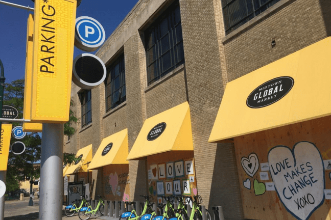 A light brick building with bright yellow awnings with the Midtown Global Market logo on it. Two racks of bright green Nice Ride bicycles are in front of the building.