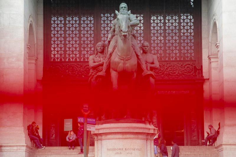 A statue of Theodore Roosevelt in front of an entrance to the American Museum of Natural History with a red line obscuring the middle third of the photograph