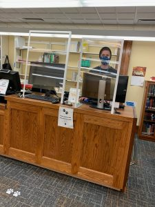 Social barriers and student worker at the circulation desk.