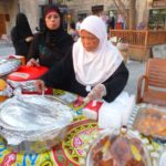 Two cooks set up outside at Doha old market.