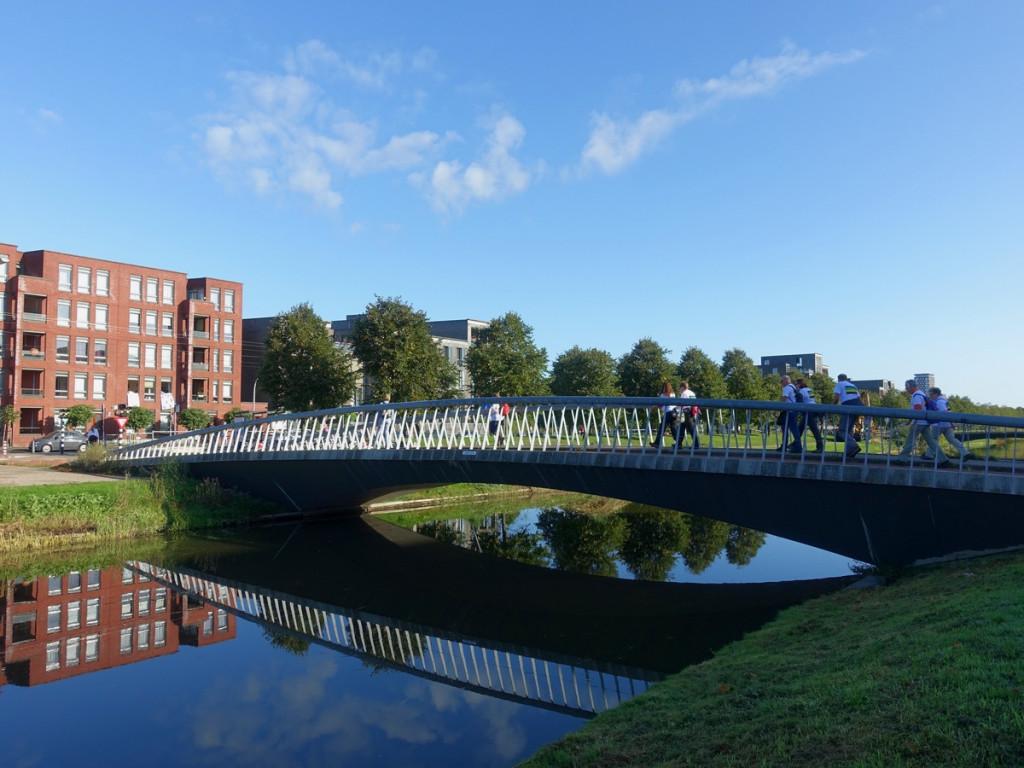 5 wandelaars over brug in woonwijk