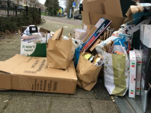 Dozen tassen en papier naast de te volle container