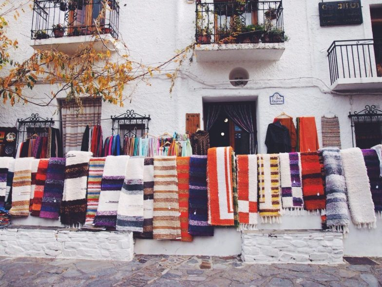 A white building with colourful carpets hanging out the front.