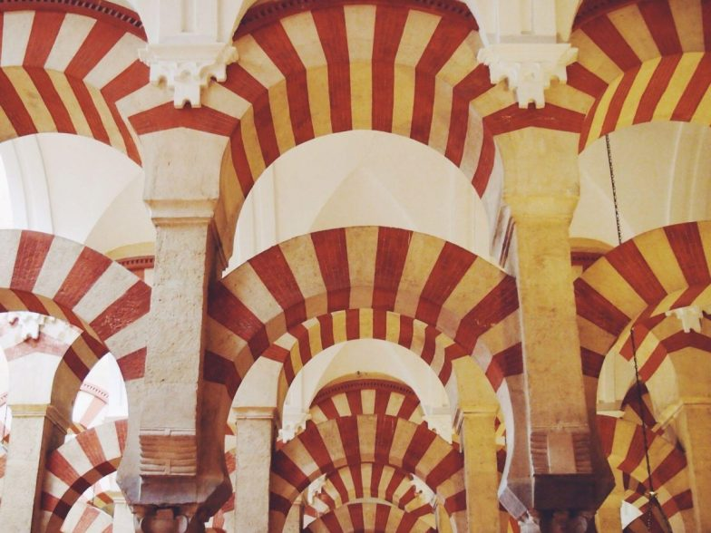 Red and white archways inside the mosque cathedral in Cordoba, Spain.