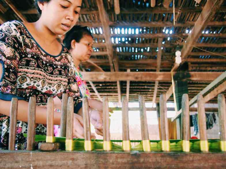 A woman stretches green-coloured silk threads on a wooden frame on Koh Dach Silk Island.
