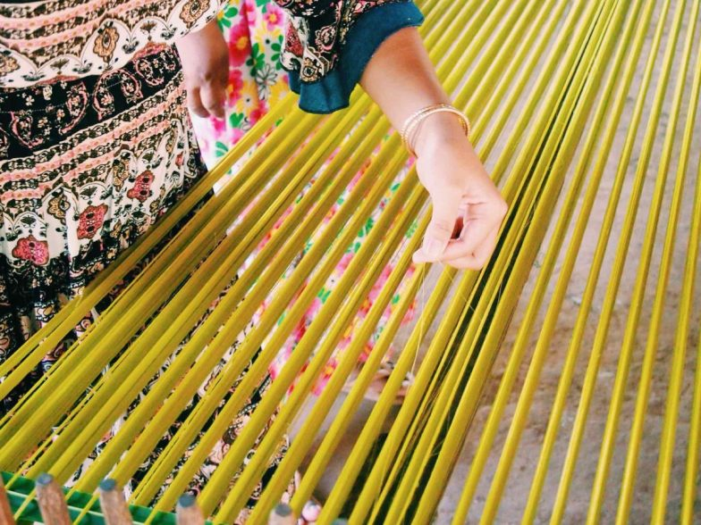 A woman stretches green-coloured silk threads on a wooden frame.