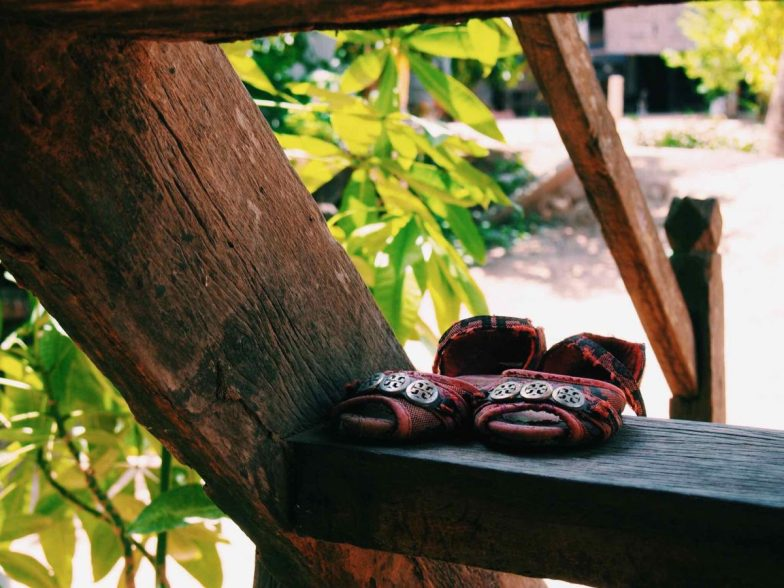 A pair of girl's shoes sitting on a wooden staircase.