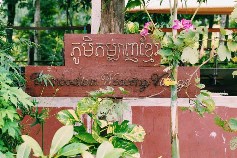 A wooden and rope sign reading Cambodian Weaving Village.