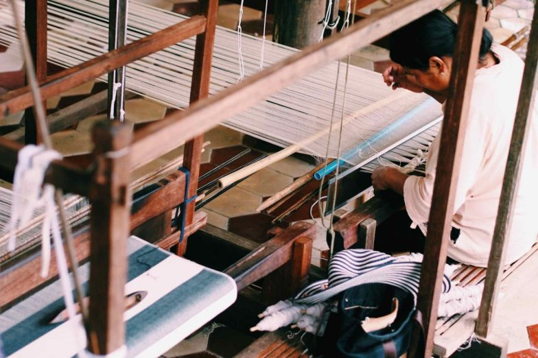 A woman weaving on an upright loom at Cambodian Weaving Village.