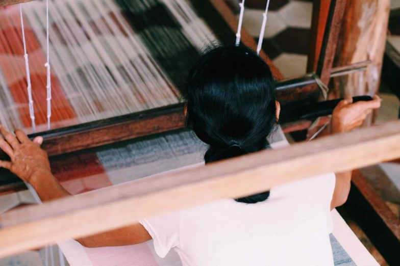 A woman weaving, pictured from behind.