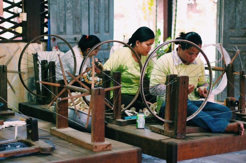 A group of women spinning fibres on wooden wheels.
