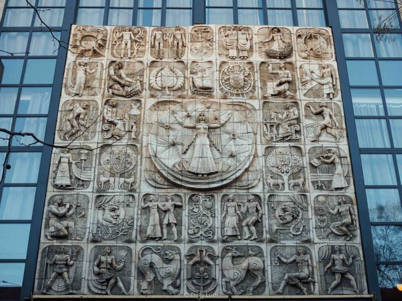A large stone sculpture depicting the signs of the Zodiac surrounded by square glass windows.