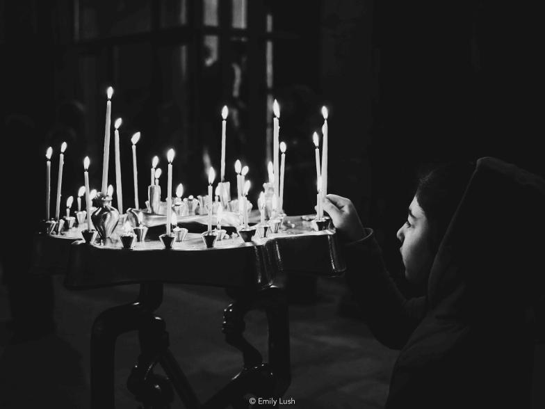 A young girl lights a candle inside an Orthodox church.