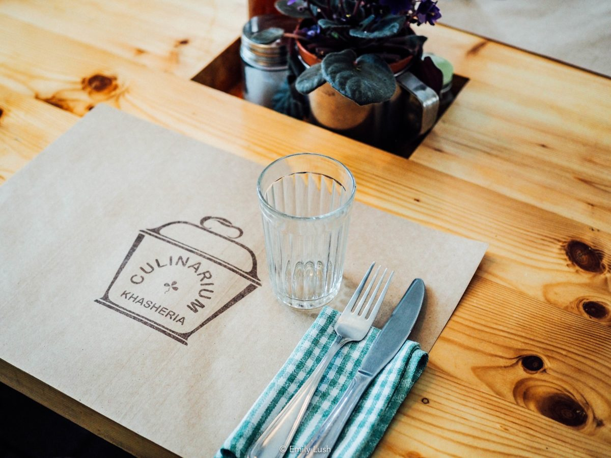A wooden restaurant table set with a placemat and cutlery.