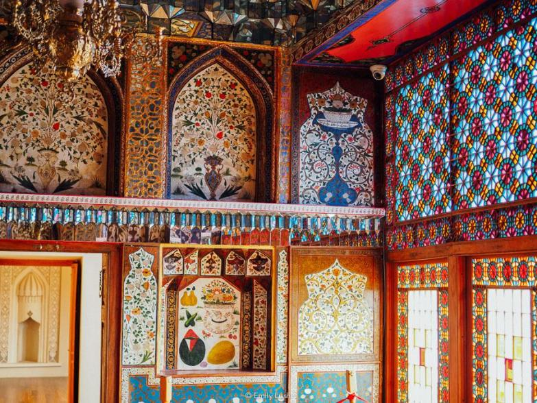 A richly decorated room with stained glass and miniature paintings.