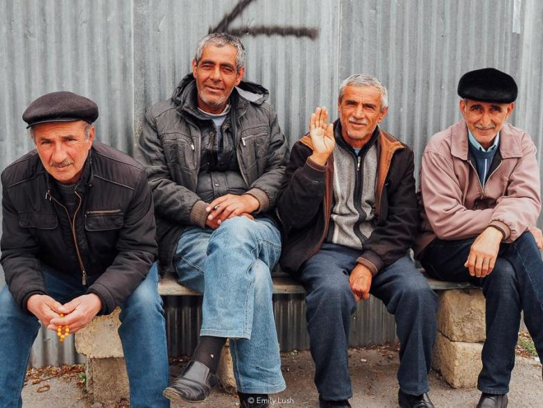 Four men sitting on a bench in front of a tin wall.
