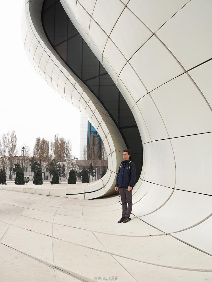 A man stands on a white curved wall.