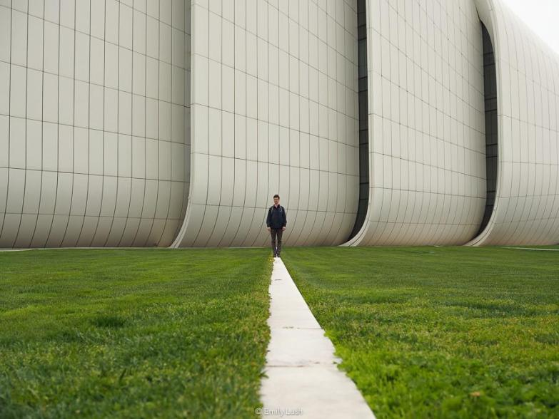 A man stands in front of the Heydar Aliyev Center on a path that cuts through a green lawn.