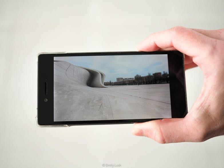 A hand holds a smart phone with an image of the Heydar Aliyev Center on the screen.