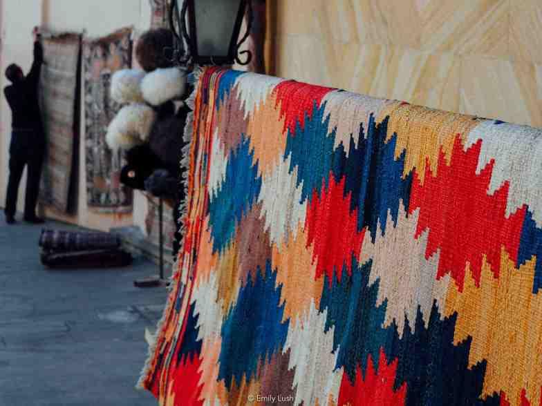 A man hangs up colourful carpets.