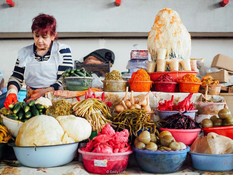 A woman in a white apron stands behind a colourful display of pickled vegetables.