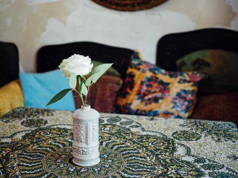 A floral tablecloth with a single rose in a vase.