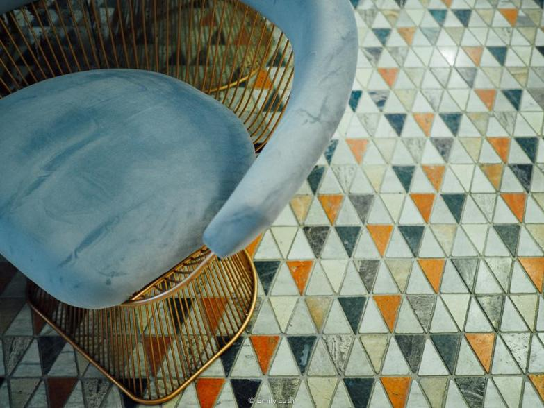 A tiled mosaic floor and a blue velvet chair.