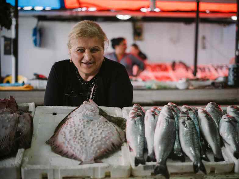 A woman stands behind a table stacked with fresh-caught fish at a market in Batumi.
